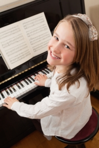 Photo of a young girl playing the piano at home.